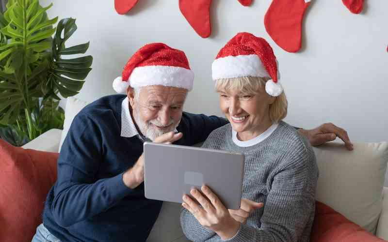 Senior man and woman visiting with family virtually during the holidays.